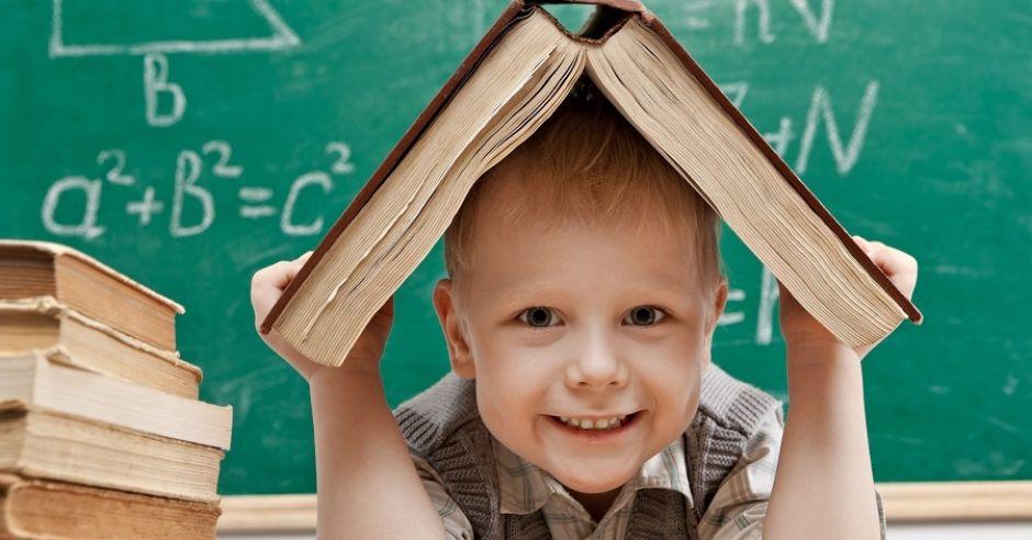 dziecko trzymające książkę nad głową na tle tablicy do pisania w klasie